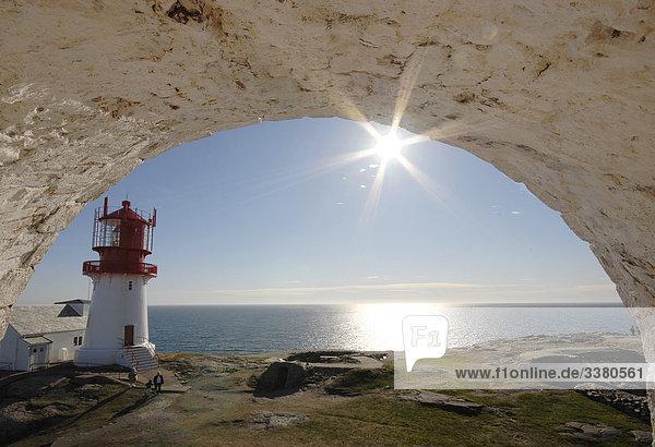 Blick durch einen Bogen auf eine Küste mit Leuchtturm  Norwegen  Erhöhte Ansicht
