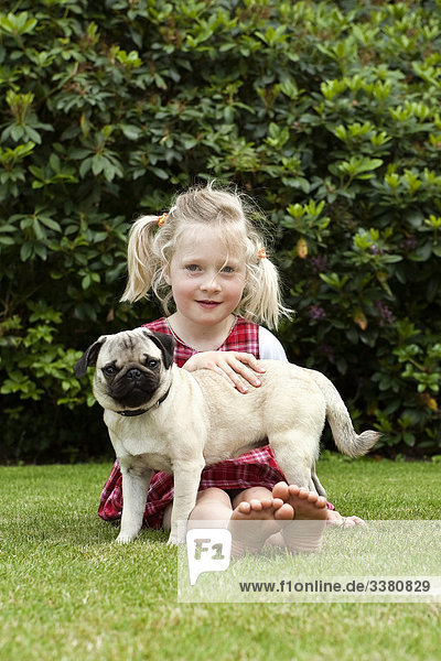 Girl sitting with pug on lawn