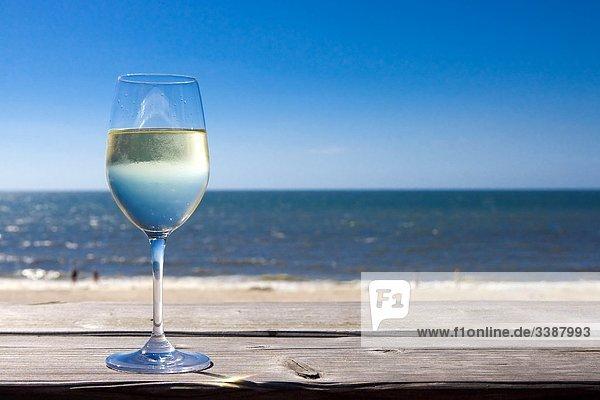 Glas mit Weißwein steht auf Holzbrett  Meer im Hintergrund  Wenningstedt-Braderup  Sylt  Deutschland