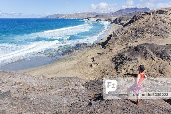 Frau auf einem Felsen an der Westküste von Fuerteventura  Spanien  Erhöhte Ansicht