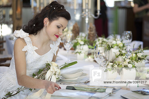 Bride sitting at a table  looking in a magazine