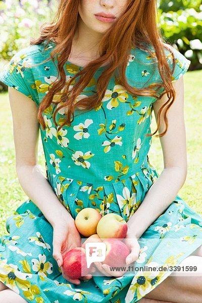 Frau  die Äpfel im Schoß hält.