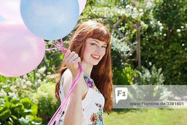 junge Frau hält Luftballons im Garten.