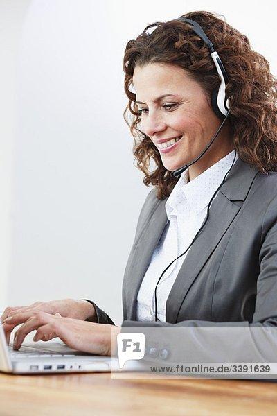 weibliche Call-Center-Agentin beim Tippen