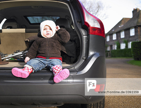 Baby sitting in open car boot