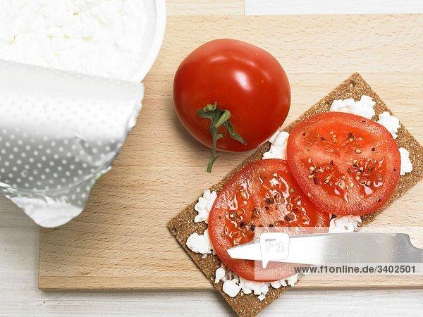 Knäckebrot mit Frischkäse  Tomaten und Pfeffer auf Holzbrett mit Messer