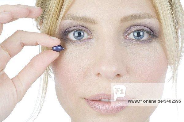 Frau hält Cremekapsel ans Gesicht