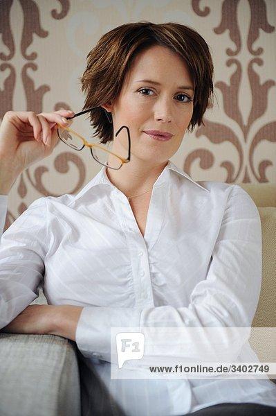 Brünette Frau hält eine Brille