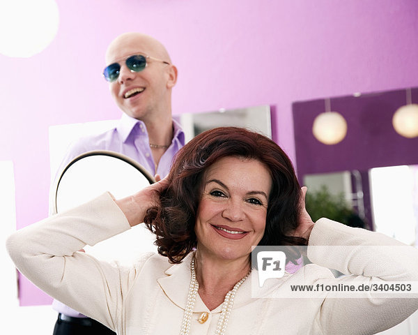 portrait of mature woman at hair salon with hair dresser in background