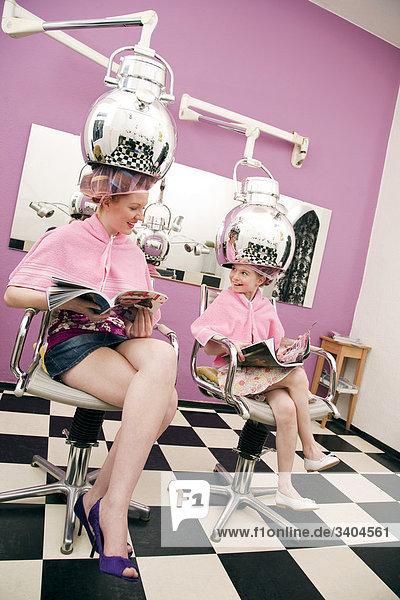 junge Frau und kleine Mädchen sitzen unter Haartrockner im Haarsalon