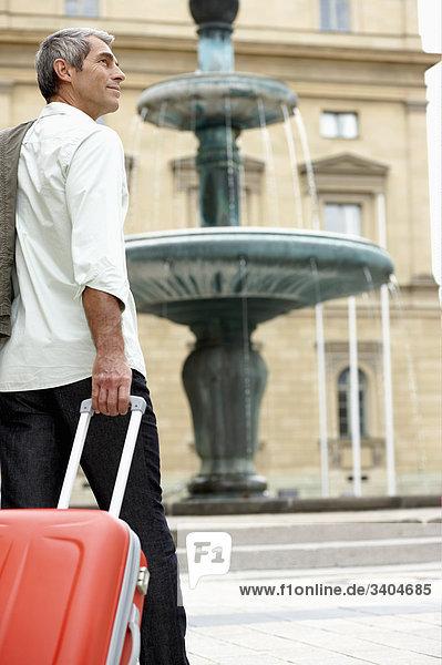 Mann zu Fuß durch Stadtstraße ziehen Handgepäck