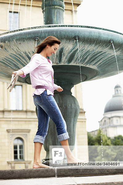 junge Frau barfuss laufen auf Brunnen