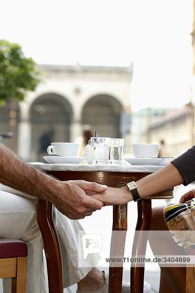 Detail des Paares sitzen an Cafe Tisch Hände