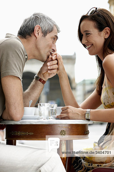 paar sitzen an Cafe Mann küssen Woman´s hand
