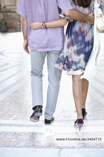 Rückansicht des jungen Paares zu Fuß