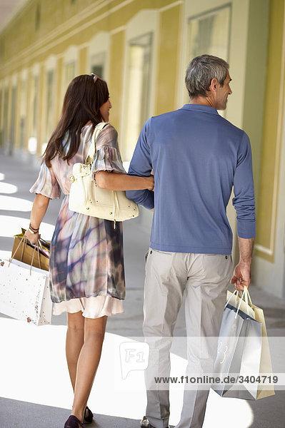 Rückansicht des Paares Einkaufstaschen tragen