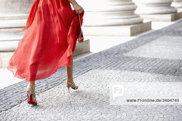 Detail der junge Frau im roten Kleid ausgeführt durch Arkaden des Theaters