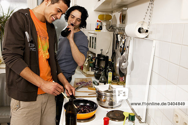 two young men in kitchen cooking together