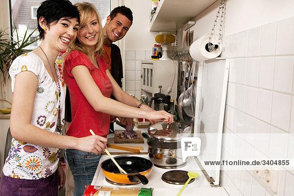 drei Freunde in Küche kochen zusammen