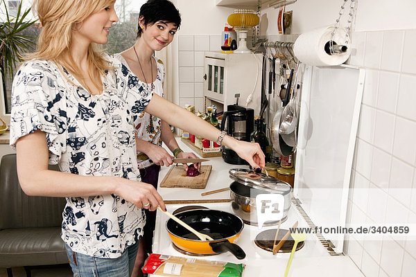 two young women cooking together in kitchen
