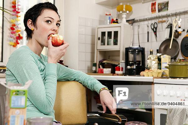 Porträt von Teenagerin sitzen in Küche Essen apple
