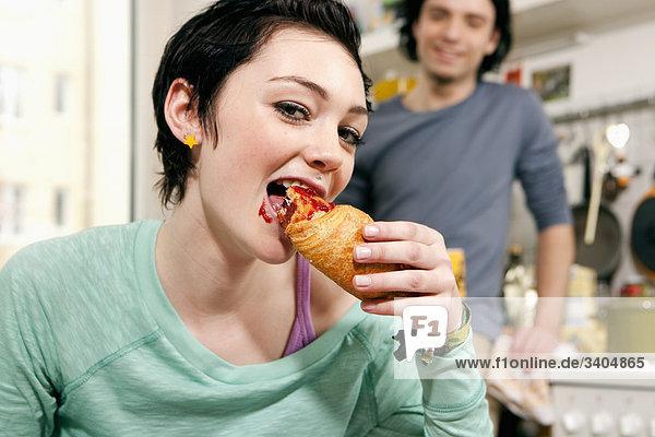 Porträt von Teenagerin essen croissant