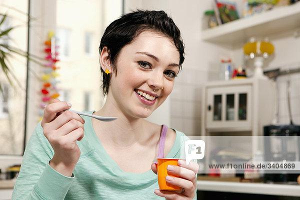 Porträt von Teenagerin essen Joghurt