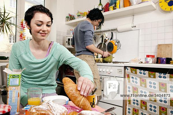 Porträt von Teenagerin am Frühstückstisch während Freund Spülbürste ist