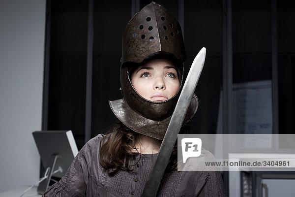 junge Frau im Büro tragen Rüstung und Schwert