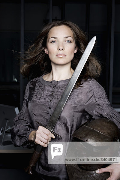 Portrait einer Frau in Office mit Helm und Schwert