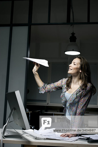 junge Frau im Büro spät in die Nacht spielen mit Papierflieger