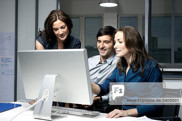 Gruppe von drei sitzen vor Computer Geschäftsleute