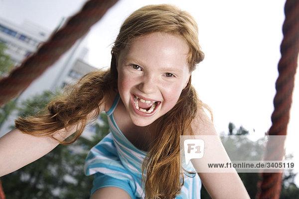 Porträt des jungen Mädchens Kletterseile auf Spielplatz
