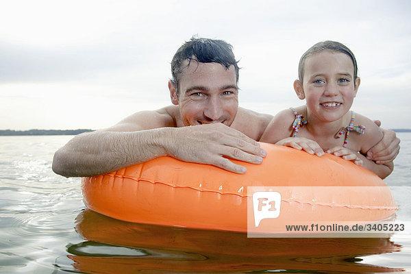 Portrait von jungen Mädchen und Vater Schwimmen mit schwimmenden Reifen