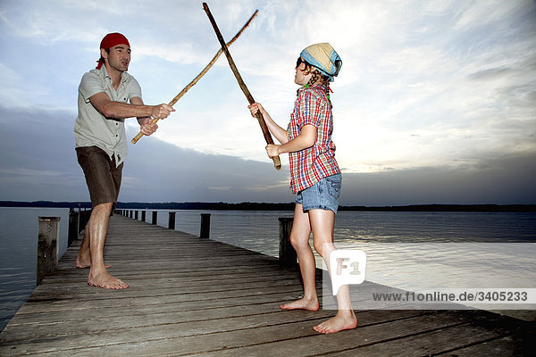 junge Mädchen und Vater getarnt als Piraten kämpfen mit hölzernen