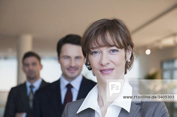 Geschäftsfrau lächelt in die Kamera  zwei Geschäftsmänner dahinter