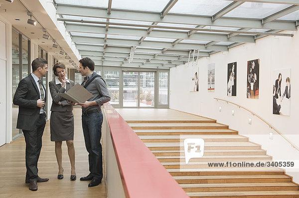 Drei Personen stehen im Bürogebäude