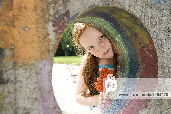 jungen Mädchen wird durch Loch in der Wand auf Spielplatz