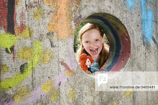 Porträt von lachend Mädchen auf der Suche durch Loch in der Wand auf Spielplatz