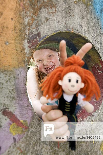 Porträt von lachend Mädchen auf der Suche durch Loch in der Wand auf Spielplatz halten doll