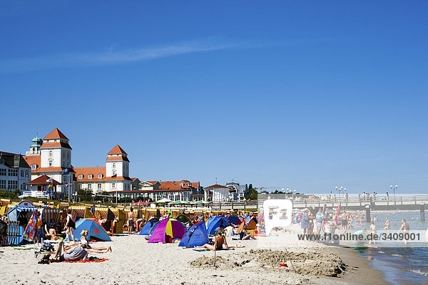 Tourists on the beach of Binz  spa hotel in the background  Ruegen  Germany