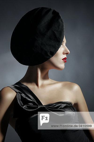 Junge Frau mit schwarzem Kleid und Hut