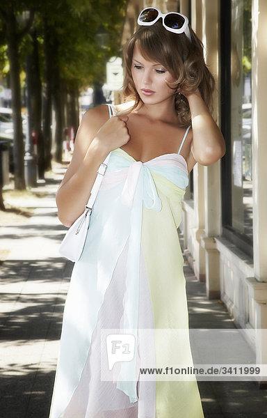 Junge Frau in weißem Sommerkleid mit Handtasche und Sonnenbrille