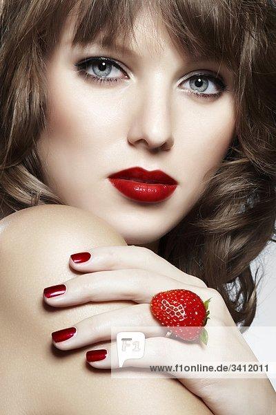 Junge Frau mit einem Ring aus einer Erdbeere mund