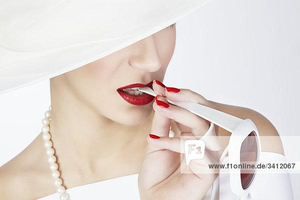 Junge Frau mit weißem Hut beißt auf Sonnenbrille mund