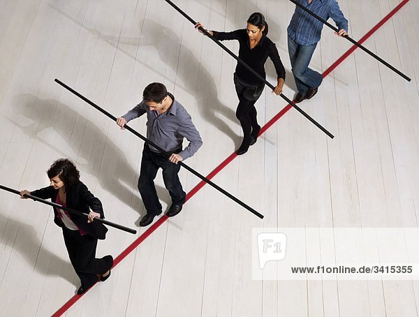 Menschen balancieren auf dünner roter Linie
