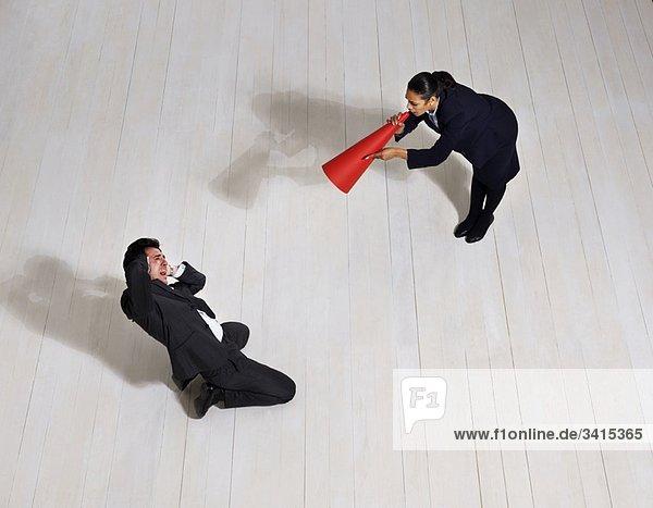 Geschäftsfrau schreit den Mann auf dem Boden an.