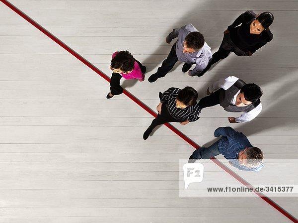 Geschäftsleute überqueren eine rote Linie