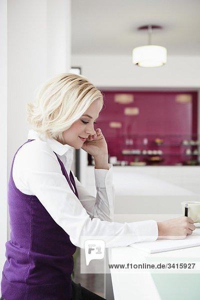 Frau beim Schreiben im Cafe