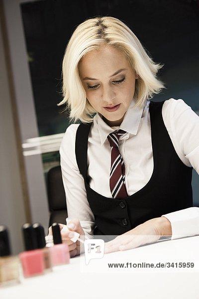 Blonde Frau poliert Nägel